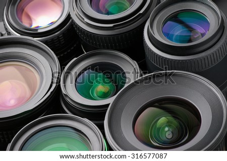 Close-up of many various photo lenses with colorful antireflection multi-layer coating. - stock photo