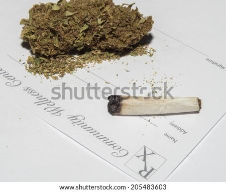 close up of marijuana cigarettes and medical marijuana card - stock photo