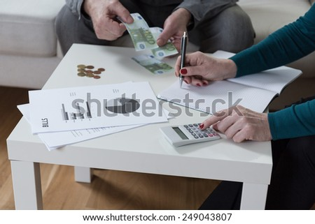 Close-up of marriage writing down their expenses - stock photo