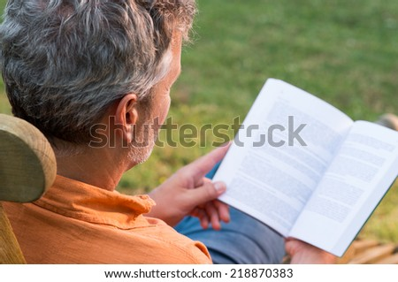 Close-up Of Mature Man Sitting On Lounge Chair Reading Book Outdoor - stock photo
