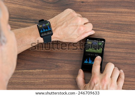 Close-up Of Mature Man With Smartwatch And Cellphone Showing Heartbeat Rate Sitting At The Table - stock photo