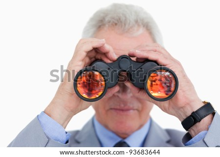 Close up of mature tradesman looking through spy glass against a white background - stock photo