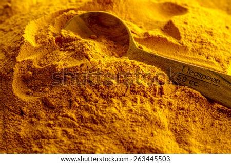 Close up of measuring spoon in pile of organic turmeric (curcuma) powder - stock photo
