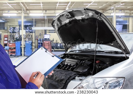 Close-up of mechanic maintaining car record on clipboard at the repair shop - stock photo