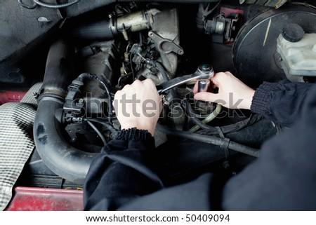 Close-up of mechanic repairing an engine - stock photo