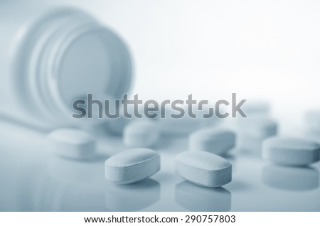 Close-up of medicine tablets spilled from bottle - stock photo