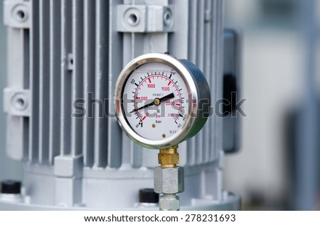 Close up of metal manometer with machinery in background - stock photo