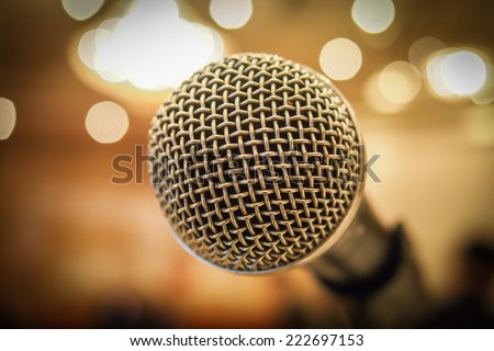 Close up of microphone in concert hall or conference room with lights in background. Macro with extremely shallow dof. - stock photo