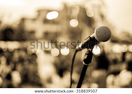Close up of microphone in concert or conference room with blur people in the background. Retro Style - stock photo