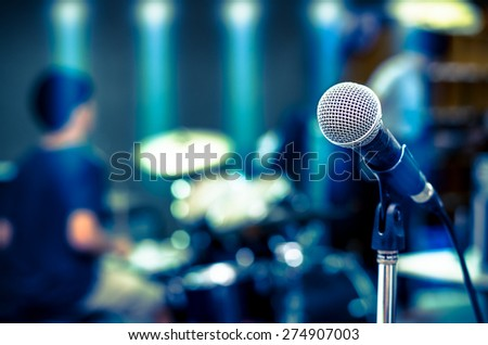 Close up of microphone on musician blurred background - stock photo