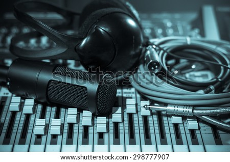 Close up of microphone with headphone on mixer, music instrument concept - stock photo