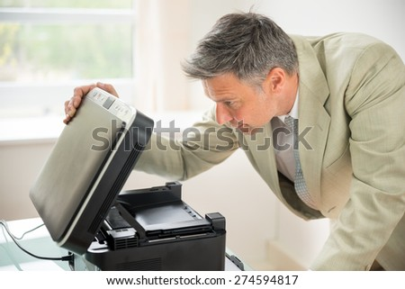 Close-up Of Mid-adult Businessman In Office Looking At Photocopy Machine - stock photo