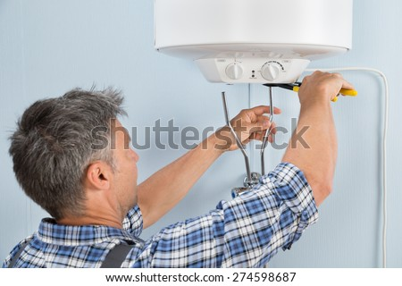 Close-up Of Mid-adult Male Plumber Installing Water Heater - stock photo