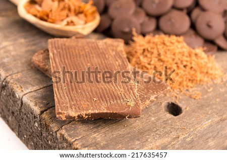 Close up of milk chocolate bar shredded chocolate and bonbons on a wooden table selective focus - stock photo