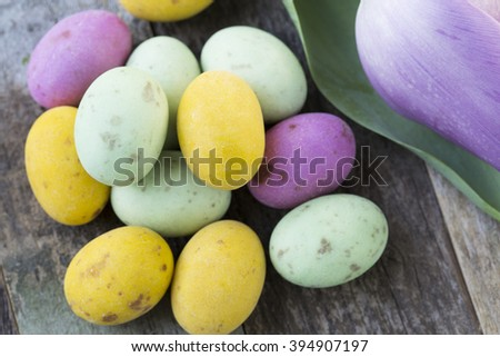 Close up of milk chocolate eggs on table with flowers. - stock photo