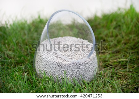 Close up of mineral fertilizer for soil in glass pot in the grass - stock photo