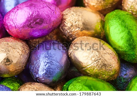 Close up of mini chocolate eggs wrapped in colourful foil - stock photo