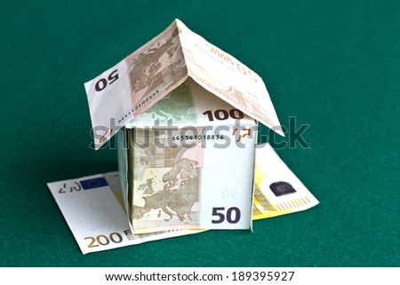 Close up of miniature house built of paper currency on green background  - stock photo