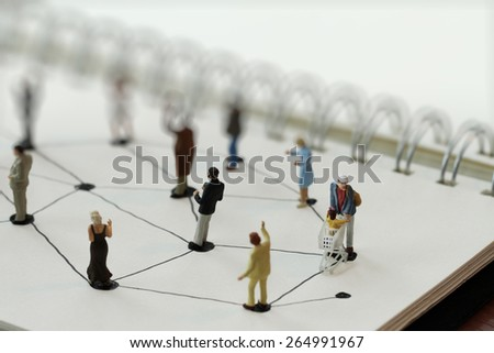 close up of miniature people with social network diagram on open notebook on wooden desk as social media concept, soft focus - stock photo