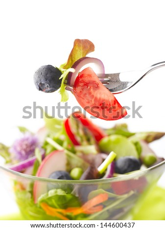 Close up of mixed vegetable and fruit salad on fork. Shallow focus - stock photo