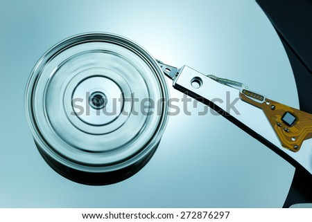 Close up of modern opened hard disk drive with spinning platter - stock photo