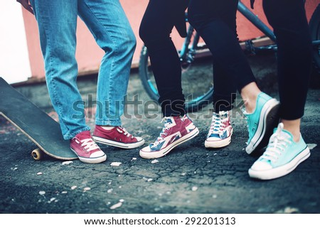 Close up of modern sneakers worn by friends, urban lifestyle of modern clothing and footwear - stock photo