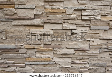 Close up of modern style design decorative uneven cracked real stone wall surface with cement - stock photo