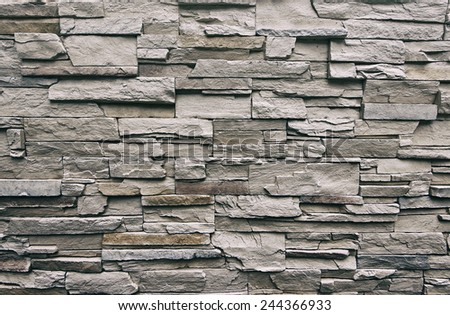 Close up of modern style design decorative uneven cracked real stone wall surface with cement, old vintage - stock photo