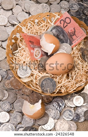 close up of money with eggs in nest - australian currency notes and coins - stock photo