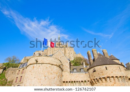 close up of Mont Saint Michel with french flag,  France - stock photo