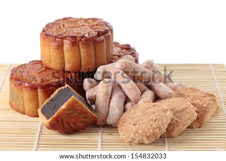 Close up of mooncakes and mid autumn pastry on bamboo mat. (The chinese words indicates the type of mooncake, not the brand) - stock photo