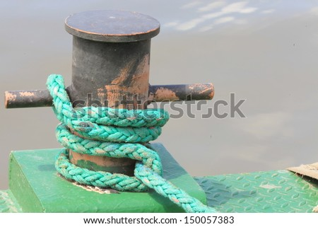 Close-up of mooring bollard with green rope in marina. - stock photo