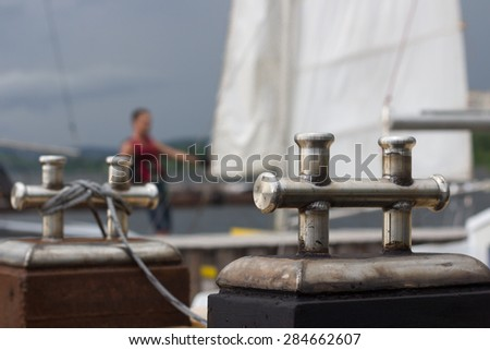 Close-up of mooring bollard with  rope in marina - stock photo