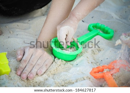 Close up of mother and daughter hands on sand - stock photo