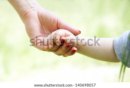 Close up of mother holding son by hand - stock photo