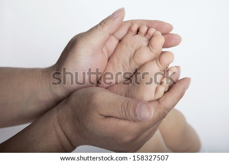 Close up of mothers hands holding the feet of her son - stock photo