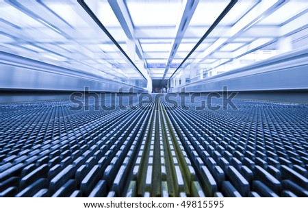 Close-up of moving escalator in blue corrior - stock photo