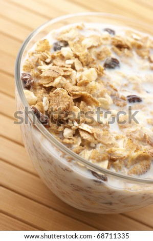 Close-up of muesli with milk in glass bowl on wooden surface. - stock photo