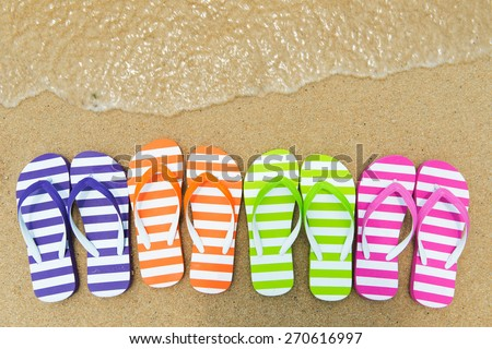 Close up of multicolor flip flips on sand - stock photo