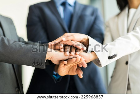 close up of multiracial business people putting their hands together, focus on hands - stock photo