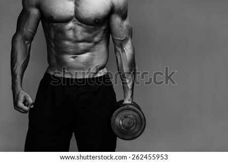 Close up of muscular bodybuilder guy doing exercises with weights over grey background. Black and white - stock photo