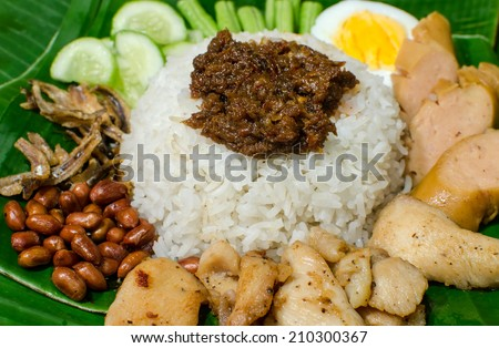 Close up of Nasi lemak kukus traditional Malaysian Spicy Rice dish, fresh cooked with hot steam. Served with Belacan, ikan bilis, acar, Peanuts and Cucumber. Decoration setup. - stock photo