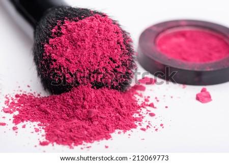 Close-up of  natural  black bristle of professional  make-up brush with crashed pink eyeshadow lying near opened single pink eyeshadow  pot  isolated on white background - stock photo