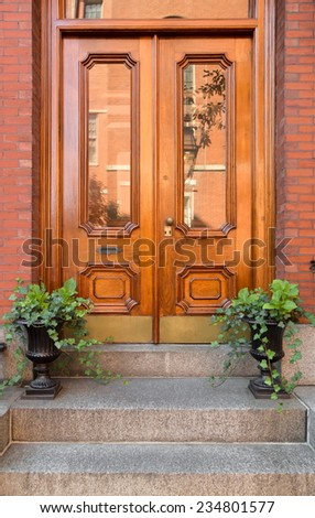 Close Up of Natural Wood Double Front Doors with Inset Windows and Greenery  - stock photo