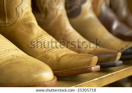 Close-up of new cowboy boots on shelf. - stock photo