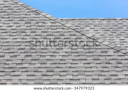Close up of new rubber roof tiles with blue skybackground. - stock photo