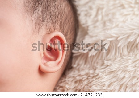 close up of newborn baby ear, showing close up of ear and side of babies head - stock photo