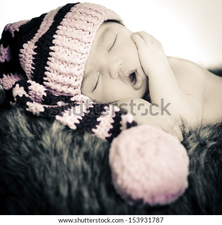 Close up of Newborn baby girl sleeping wearing pink/brown hat, on fur and white background. Black and White. - stock photo