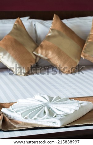 Close up of nice towels on white bed sheet with golden pillow - stock photo