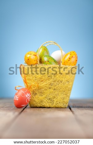 Close up of nicely decorated Easter egg in grass. Wooden background. - stock photo